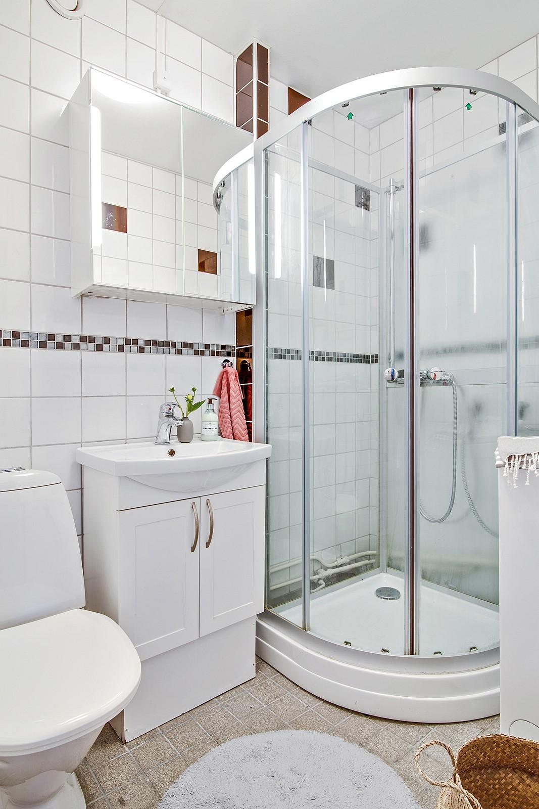 Helkaklat och ljust badrum som är utrustad med uppskattad tvättmaskin